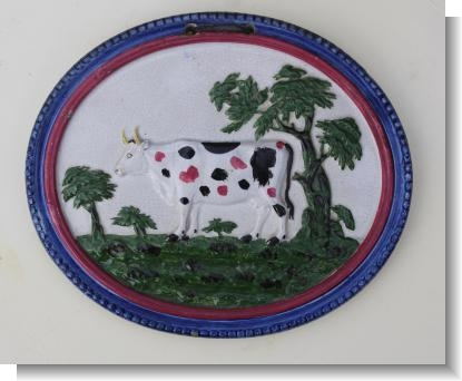 PEARLWARE COW PLAQUE decorated in over glaze colours, c.1820-25